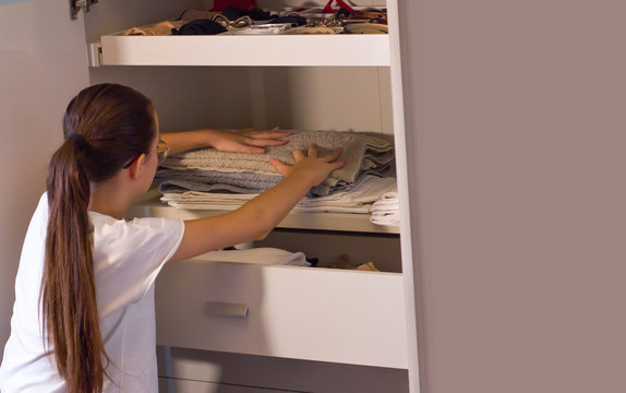 Teen girl order the linens in the closet. Concept of order, cleanliness in wardrobe and home, collaboration of the teenagers to keep the home environments tidy.