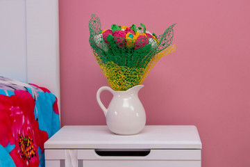 jug with flowers near the bed, artificial flowers in the bedroom on the bedside table