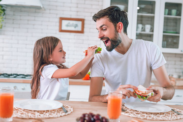 girl feeding father eating with her sandwich for breakfast on the kitchen