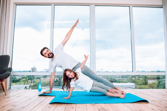 happy girl and her father doing yoga at home using yoga mats