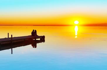 Wall Mural - pareja de enamorados mirando la puesta de sol en la playa