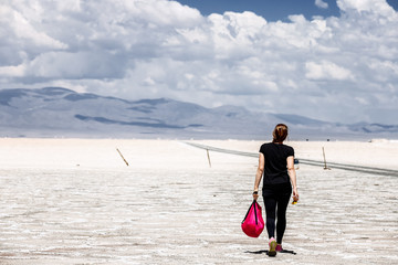 Young woman walks with her backpack in the Salinas Grandes salt flats in Jujuy, Argentina