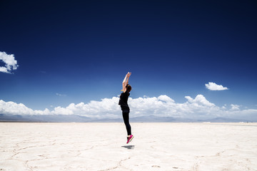 Young woman jumps straight in the Salinas Grandes salt flats in Jujuy, Argentina