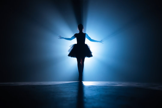 Young beautiful ballerina on smoke stage dancing modern ballet. Performs smooth movements with hands against spotlight background. Woman in black tutu costume on scene.