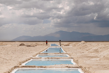 Two female tourists walk among the pools in the Salinas Grandes salinas in Jujuy, Argentina