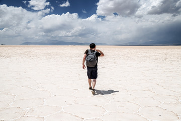 Young man walking with his backpack on the salt flats in the Salinas Grandes in Jujuy, Argentina
