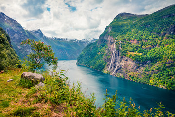 Sublime summer scene of Sunnylvsfjorden fjord, Geiranger village location, western Norway. Beautiful morning view of famous Seven Sisters waterfalls. Beauty of nature concept background.