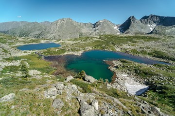 Wall Mural - Wild russian nature. Beautiful landscape with emerald lake in the mountains. Lake with clear turquoise water. Traveling in the Altai Republic. Tourism in Russia. Siberian reserve. Summer hiking.