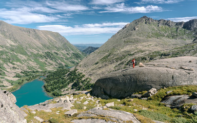 Wall Mural - Wild russian nature. Panoramic landscape with emerald lake in the mountains. Lake with turquoise water. Traveling in the Altai Republic. Tourism in Russia. Man looking at the horizon. Alpine scenery.