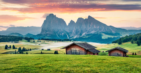 Perfect morning scene of Compaccio village, Seiser Alm or Alpe di Siusi location, Bolzano province, South Tyrol, Italy, Europe. Attractive summer sunrise of Dolomiti Alps. Wall mural