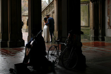 A couple kisses as they have their wedding pictures taken near the Bethesda Fountain in New York's Central Park