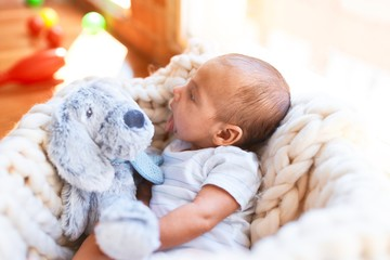 Adorable baby lying down over blanket on the floor at home. Newborn relaxing and resting comfortable with teddy bear