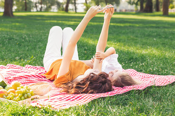 woman and girl taking selfie on smartphone while lying on the picnic blanket in the park