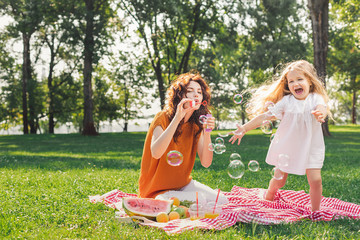 attractive woman blowing sopa bubbles while girl playing with them in the park