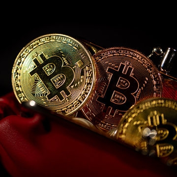 Gold metal Bitcoins in red leather wallet on black background