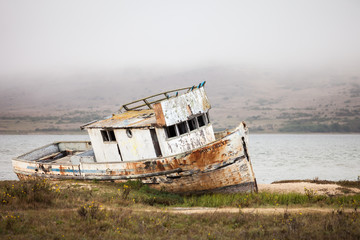 An old broken down boat by a bay