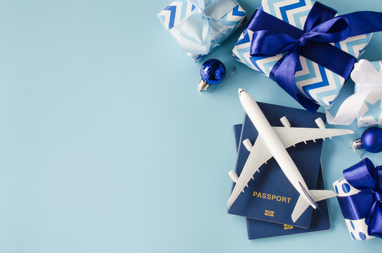 Travel present for Christmas or New Year. Toy airplane with passports and gift boxes.