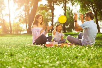 father, mother and daughter playing with balloon in the park