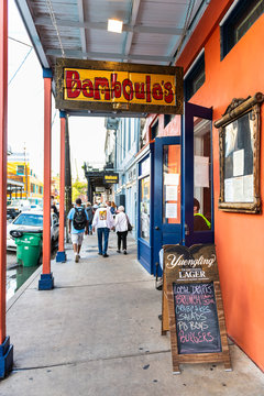 New Orleans, USA - April 22, 2018: Frenchmen street covered sidewalk in French Quarter, Louisiana old town city with sign for Bamboula's southern creole restaurant