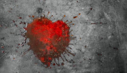 red puddle in the shape of a broken heart on a gray concrete background