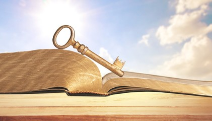 Wall Mural - Open book on old wooden table on sky background sunlit