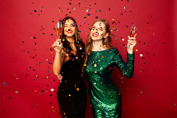 two beautiful models, a redhead and a brunette in New Year's dresses, having fun and smiling with glasses of champagne, confetti flying around on a red background. New Year or Christmas photo