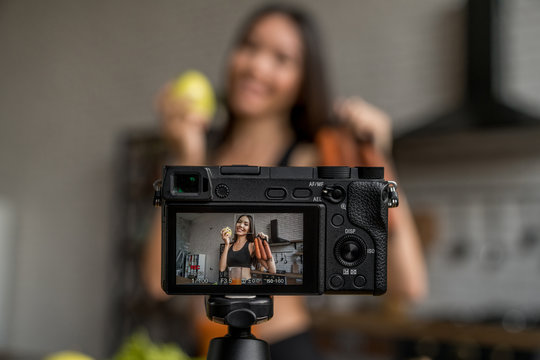 Camera showing woman with fruits and vegetables in hand while woman recording video