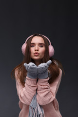 Portrait of young beautiful smiling girl in knitting pullover, mittens and pink fluffy earmuffs on a dark background. Xmas model with long straight hair. Winter holidays, Christmas, New Year concept.