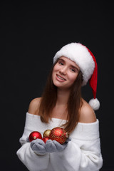 Young beautiful smiling girl in red Santa hat holding Christmas balls on a dark background. Xmas fashion model with long straight hair. Winter holidays, Christmas, New Year concept.