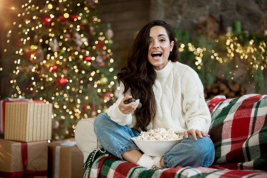 brunette woman wearing sweater watching comedy sitting on the sofa with popcorn in room decorated for celebrating new year and christmas eve