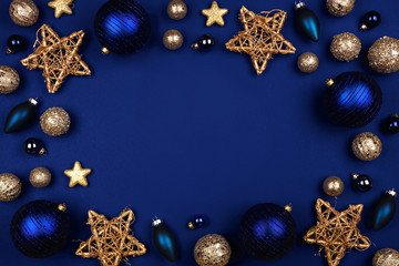 Christmas frame of dark blue and gold ornaments. Above view on a midnight blue background.