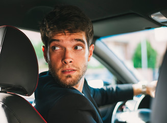 Attractive young man with a beard drives reverse.