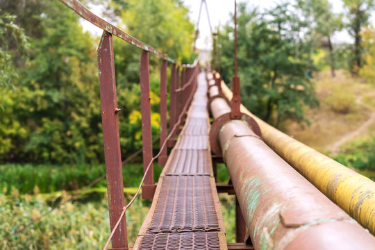 A narrow old rusty river crossing, along with a water and gas pipe. Communications in the village.