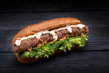 Photo sur Aluminium Snack close up of kebab sandwich on black wooden background
