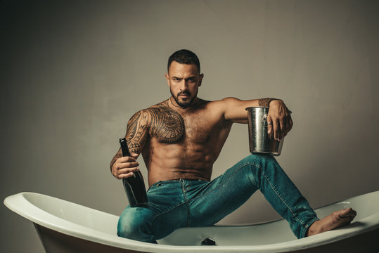 Handsome bearded shirtless man in jeans with sexy body in bathroom. Sexual macho man in bath. Strong muscular tattoed man holding champagne bottle and posing in bathroom.