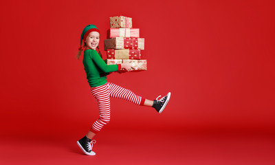 cheerful funny child in Christmas elf costume with gifts on   red background.