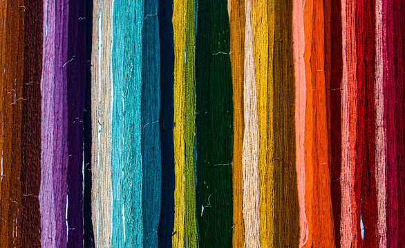 Colorful rainbow of freshly hand dyed yarn hanging on a wall