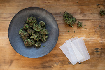 Still life of marijuana in bowl with rolling papers