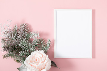 Christmas holiday composition. Photo frame, fir tree branches, flowers on pastel pink background. Christmas, New Year, winter concept. Flat lay, top view, copy space