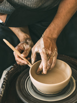 Ceramist at a pottery workshop Man is sculpting a bowl behind a rotating potter's wheel