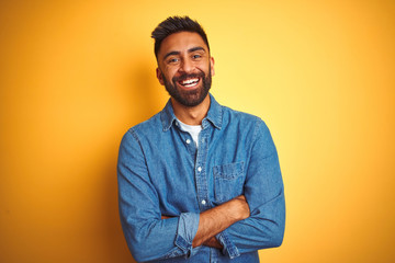 Young indian man wearing denim shirt standing over isolated yellow background happy face smiling with crossed arms looking at the camera. Positive person. Fotobehang
