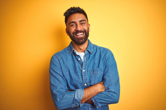 Young indian man wearing denim shirt standing over isolated yellow background happy face smiling with crossed arms looking at the camera. Positive person.