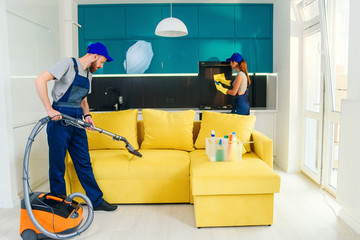 Young man vacuums yellow sofa and cute girl wiping kitchen furniture. Professional cleaners in apartment.