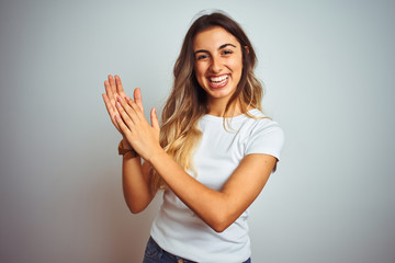 Young beautiful woman wearing casual white t-shirt over isolated background clapping and applauding happy and joyful, smiling proud hands together