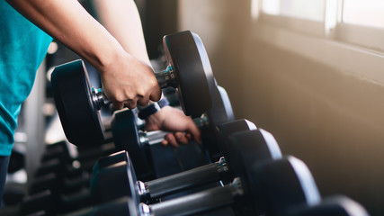 hands of man lifting dumbbells on rack in gym or fitness