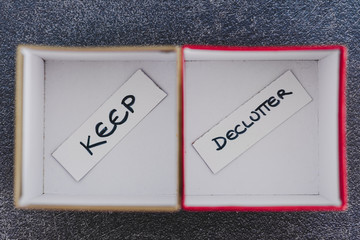 tidying up conceptual still-life, storage boxes with Keep and Declutter labels on them next to each other