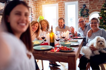 Family and friends dining at home celebrating christmas eve with traditional food and decoration, taking a selfie picture together