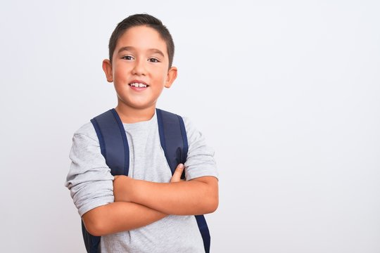 Beautiful student kid boy wearing backpack standing over isolated white background happy face smiling with crossed arms looking at the camera. Positive person.