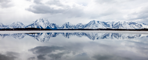 Panoramic View of Reflection of Mountain Range in Lake at Grand Tetons National Park in Wyoming, USA