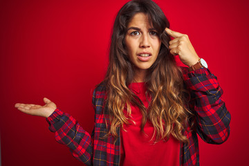 Young beautiful woman wearing casual jacket standing over red isolated background doing funny gesture with finger over head as bull horns